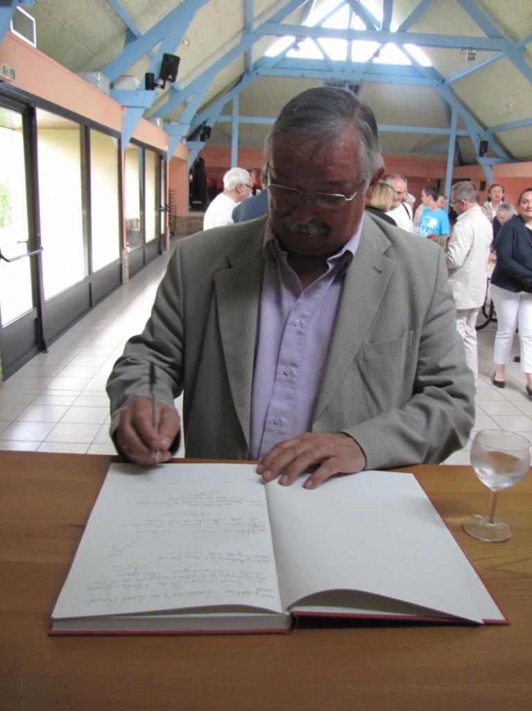 M. Jean-Jacques Hilmoine, Président de la Communauté de Communes du Canton de Fruges, anotant le livre d'or de l'église de Fressin.