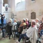 Le public installé dans la chapelle de l'église, face au retable